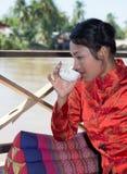 Asiatisches Mädchen, das von einer Schale trinkt stockbild