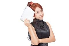 Asiatisches Mädchen denkt mit einem Buch in ihrer Hand Lizenzfreies Stockfoto