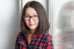 Asiatisches Mädchen der Schönheit, das auf Fensterbrett sitzt Lizenzfreie Stockbilder