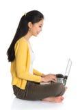 Asiatisches Mädchen der Seitenansicht, das Notebook verwendet Stockfoto