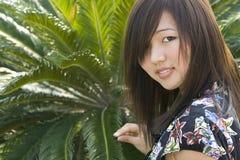 Asiatisches Mädchen des Brunette mit grüner Palme Stockfotografie