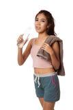 Asiatisches Mädchen des müden Trainings mit Flasche des Wassers und des Tuches Stockfotografie