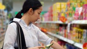 Asiatisches Mädchen, Fraueneinkaufssnäcke im Supermarkt Lizenzfreies Stockfoto