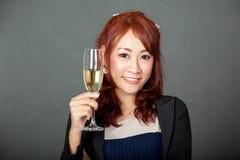 Asiatisches Mädchen glücklich mit einem Glas Weißwein in ihrer Hand Lizenzfreie Stockfotos