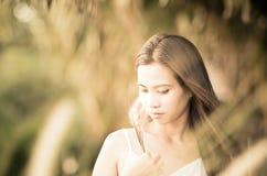 Asiatisches Mädchen am Grasfeld am Sonnenuntergang. Stockfotografie