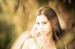 Asiatisches Mädchen am Grasfeld am Sonnenuntergang. Lizenzfreies Stockbild