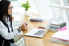 Asiatisches Mädchen im coworking Sitzen im modernen coworking Büro unter Verwendung des Radioapparates 5G Stockfotografie