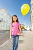 Asiatisches Mädchen mit dem Fliegenballon, der auf Straße steht Lizenzfreie Stockfotografie