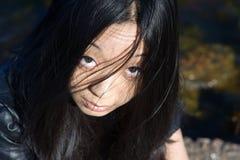 Asiatisches Mädchen mit dem Haar auf Gesicht Stockfotos
