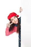 Asiatisches Mädchen mit dem roten Weihnachtshut, der von hinten leeres bann späht Lizenzfreies Stockfoto