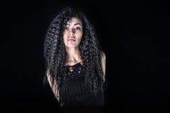 Asiatisches Mädchen mit dem schönen gelockten Haar im schwarzen Kleid Stockfotografie