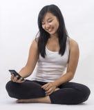 Asiatisches Mädchen mit einem intelligenten Telefon stockfoto