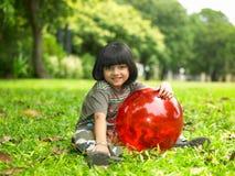Asiatisches Mädchen mit ihrer rosafarbenen Kugel Stockbild
