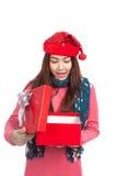 Asiatisches Mädchen mit offener Geschenkbox des roten Weihnachtshut-Lächelns Stockbild