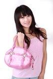 Asiatisches Mädchen mit rosafarbener Handtasche Stockfotografie