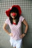 Asiatisches Mädchen mit roter Wekzeugspritze und Hut Stockbild