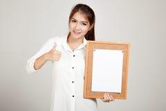 Asiatisches Mädchen mit Stift des leeren Papiers vom Korkenbrett stockbild