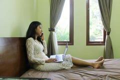 Asiatisches Mädchen oder Frau, die am intelligenten Telefon beim Legen in Bett sprechen Stockbilder
