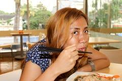 Asiatisches Mädchen oder Frau, die Nudeln mit Essstäbchen im Restaurant essen Lizenzfreie Stockfotos