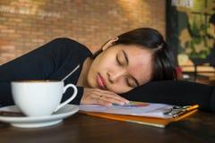 Asiatisches Mädchen schlafen auf Dokument ein lizenzfreie stockbilder