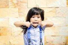 asiatisches Mädchen spielen ihren Mund, der in der blauen Reihe furchtsam ist Lizenzfreie Stockfotos