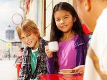 Asiatisches Mädchen und blonder Junge, die draußen im Café sitzt Lizenzfreies Stockbild