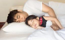 Asiatisches Mädchen und Vater, die auf Bett schläft lizenzfreies stockfoto