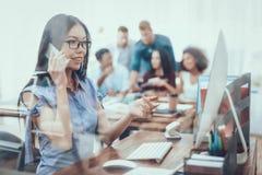Asiatisches Mädchen unterhaltung telefon arbeit Großes Büro lizenzfreie stockfotos