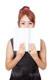 Asiatisches Mädchen verstecken ihren Mund mit einem Buch Lizenzfreie Stockfotos