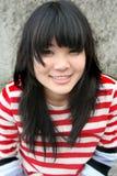 Asiatisches Mädchen, welches das bunte Streifenlächeln trägt Stockbilder