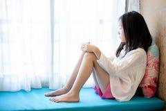 Asiatisches Mädchen, welches das Fenster im Haus wartet, sitzt und betrachtet stockbild