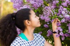 Asiatisches Mädchen, welches die Blumen riecht Stockbild