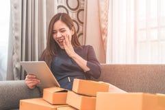 Asiatisches Mädchen wird zum on-line-Einkaufen gewöhnt, das von den Kästen voll ist lizenzfreies stockfoto