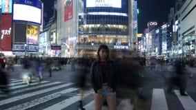 Asiatisches Mädchen Zeit Lapce, das an gedrängter Shibuya-Überfahrt, Tokyo, Japan aufwirft stock footage