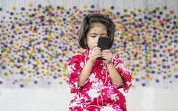 Asiatisches Mädchenlächeln mit Kopfhörer und Handy stockbilder