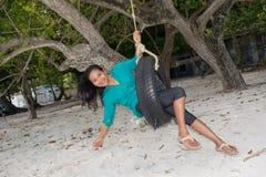 Asiatisches Mädchenreiten auf dem Schwingen gemacht vom Reifen am Strand Stockfotografie