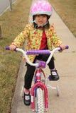 Asiatisches Mädchenreitenfahrrad Stockfotografie