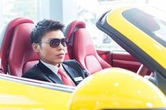 Asiatisches Mannprüfungs-Sportauto Stockfotografie