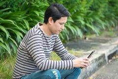 Asiatisches Mannsitzen und mit Smartphone stockfoto