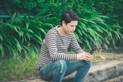 Asiatisches Mannsitzen und mit Smartphone lizenzfreie stockbilder
