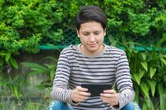 Asiatisches Mannsitzen und mit Smartphone stockfotos