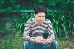 Asiatisches Mannsitzen und mit Smartphone stockbilder