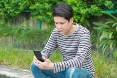 Asiatisches Mannsitzen und mit Smartphone lizenzfreies stockbild