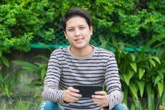 Asiatisches Mannsitzen und mit Smartphone lizenzfreie stockfotografie