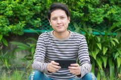 Asiatisches Mannsitzen und mit Smartphone stockfotografie