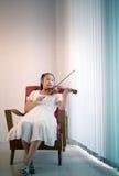 Asiatisches Mädchen, das auf Sofa in der Wohnzimmerpraxis zum Spielen der Viola liegt Stockfotos