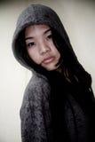 Asiatisches Mädchen, das eine Haubenjacke trägt Stockfotografie