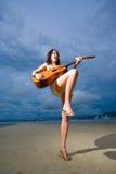 Asiatisches Mädchen, das Gitarre am Strand spielt Lizenzfreies Stockfoto