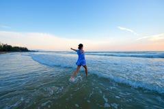 Asiatisches Mädchen, das in Richtung zum Wasser läuft Stockfotos
