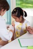 Asiatisches Mädchen während des Impfstoffs Lizenzfreies Stockbild